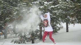 Ελκυστική νέα γυναίκα που τρέχει snowdrift που τινάζει τους χιονώδεις κλάδους που απολαμβάνουν το χειμώνα σε σε αργή κίνηση κατά  απόθεμα βίντεο