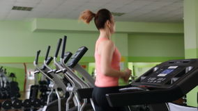 Ελκυστική νέα γυναίκα που τρέχει treadmill φιλμ μικρού μήκους