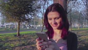 Ελκυστική νέα γυναίκα που χρησιμοποιεί το smartphone υπαίθρια φιλμ μικρού μήκους
