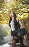 Ελκυστική νέα γυναίκα σε έναν φθινοπωρινό πυροβολισμό μόδας Όμορφη μοντέρνη κυρία στη γραπτή τοποθέτηση εξαρτήσεων στο πάρκο Στοκ Φωτογραφία