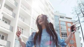 Ελκυστική νέα γυναίκα σε ένα μοντέρνο βλέμμα και άσπρα ακουστικά που ακούνε τη μουσική και που χορεύουν ελεύθερα στην πόλη φυσικό απόθεμα βίντεο