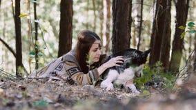 Ελκυστική νέα γυναίκα σκοτεινός-τρίχας στα εθνικά ενδύματα που βρίσκονται στην πράσινη χλόη και που κτυπούν το σκυλί της απόθεμα βίντεο