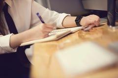 Ελκυστική νέα γυναίκα στο έξυπνο ρολόι σημειώσεων γραφείων frome στο γραφείο Στοκ φωτογραφία με δικαίωμα ελεύθερης χρήσης