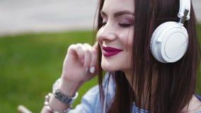 Ελκυστική νέα γυναίκα brunette σε ένα μοντέρνο βλέμμα, με τα κόκκινα χείλια και να διαπερνήσει μύτης τη συνεδρίαση στην πράσινη χ απόθεμα βίντεο