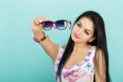 Ελκυστική νέα γυναίκα brunette στα ρόδινα γυαλιά ηλίου εκμετάλλευσης δεξαμενών τοπ στο μπλε υπόβαθρο Εστίαση στα γυαλιά Στοκ Εικόνα