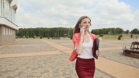 Ελκυστική νέα επιχειρησιακή γυναίκα που περπατά στο πάρκο, που μιλά στο τηλέφωνο απόθεμα βίντεο