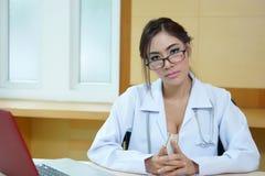 Ελκυστική νέα θηλυκή συνεδρίαση γιατρών στο γραφείο στην αρχή Στοκ εικόνες με δικαίωμα ελεύθερης χρήσης