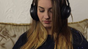 Ελκυστική νέα μουσική ακούσματος γυναικών στο smartphone φιλμ μικρού μήκους