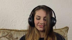 Ελκυστική νέα μουσική ακούσματος γυναικών στο smartphone απόθεμα βίντεο