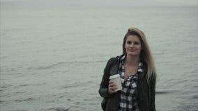 Ελκυστική νέα ξανθή γυναίκα που κρατά ένα φλιτζάνι του καφέ στα χέρια της κοντά στη θάλασσα φιλμ μικρού μήκους