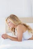 Ελκυστική νέα ξανθή γυναίκα στο κρεβάτι της Στοκ Εικόνα
