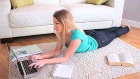 Ελκυστική νέα ξανθή μελέτη στο lap-top της απόθεμα βίντεο