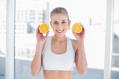 Ελκυστική νέα ξανθή πρότυπη εκμετάλλευση δύο μισά ενός πορτοκαλιού Στοκ Φωτογραφία