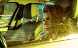 Ελκυστική νέα συνεδρίαση γυναικών πίσω από τη ρόδα Στοκ Φωτογραφίες