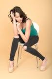 Ελκυστική νέα συνεδρίαση γυναικών σε μια έδρα στα υψηλά παπούτσια τακουνιών στοκ φωτογραφία με δικαίωμα ελεύθερης χρήσης