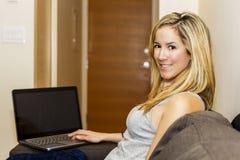 Ελκυστική νέα συνεδρίαση γυναικών στον καναπέ με το φορητό προσωπικό υπολογιστή Στοκ Φωτογραφίες
