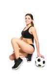 Ελκυστική νέα τοποθέτηση γυναικών με μια σφαίρα ποδοσφαίρου σε μια άσπρη πλάτη Στοκ Εικόνα