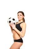 Ελκυστική νέα τοποθέτηση γυναικών με μια σφαίρα ποδοσφαίρου Στοκ Φωτογραφίες