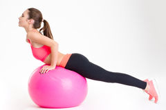 Ελκυστική νέα φίλαθλος που κάνει τις τεντώνοντας ασκήσεις στο ρόδινο fitball Στοκ εικόνες με δικαίωμα ελεύθερης χρήσης