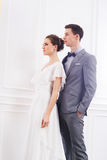 Ελκυστική νύφη σε ένα άσπρο φόρεμα και όμορφος νεόνυμφος στο γκρι Στοκ φωτογραφία με δικαίωμα ελεύθερης χρήσης