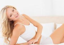 Ελκυστική ξανθή γυναίκα που βρίσκεται στο κρεβάτι που χαμογελά στη κάμερα Στοκ φωτογραφία με δικαίωμα ελεύθερης χρήσης
