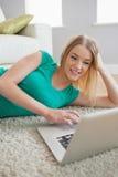 Ελκυστική ξανθή γυναίκα που βρίσκεται στο πάτωμα που χρησιμοποιεί το lap-top Στοκ φωτογραφίες με δικαίωμα ελεύθερης χρήσης