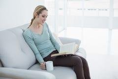 Ελκυστική ξανθή γυναίκα που χαλαρώνει διαβάζοντας ένα βιβλίο που κρατά ένα φλυτζάνι Στοκ φωτογραφία με δικαίωμα ελεύθερης χρήσης