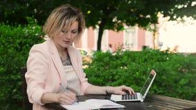 Ελκυστική ξανθή εργασία λευκών γυναικών ανεξάρτητη με το lap-top και το smartphone στο πάρκο στην ηλιόλουστη ημέρα απόθεμα βίντεο
