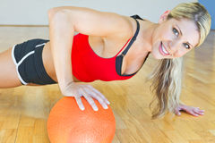 Ελκυστική ξανθή κατάλληλη άσκηση γυναικών με μια σφαίρα Στοκ Εικόνες
