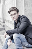 Ελκυστική ξανθή συνεδρίαση νεαρών άνδρων υπαίθρια Στοκ Εικόνες