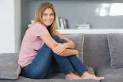Ελκυστική ξανθή συνεδρίαση στον καναπέ της Στοκ Φωτογραφίες