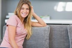 Ελκυστική ξανθή συνεδρίαση στον καναπέ της Στοκ εικόνα με δικαίωμα ελεύθερης χρήσης