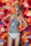 Ελκυστική ξανθή τοποθέτηση γυναικών με τα λουλούδια Στοκ εικόνα με δικαίωμα ελεύθερης χρήσης