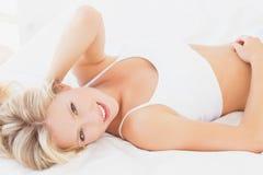 Ελκυστική ξανθή χαλάρωση γυναικών στο κρεβάτι που χαμογελά στη κάμερα Στοκ φωτογραφία με δικαίωμα ελεύθερης χρήσης
