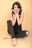 Ελκυστική προκλητική νέα γυναίκα που φορά τα μαύρες τζιν και την κορυφή φανέλλων Στοκ φωτογραφία με δικαίωμα ελεύθερης χρήσης