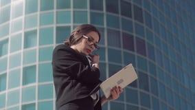 Ελκυστική σκοτεινός-μαλλιαρή επιχειρησιακή γυναίκα που φορά τα γυαλιά που χρησιμοποιούν την ταμπλέτα της για να εργαστεί υπαίθρια απόθεμα βίντεο