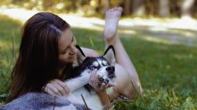 Ελκυστική σκοτεινός-μαλλιαρή νέα γυναίκα που αγκαλιάζει το σκυλί της απόθεμα βίντεο