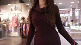 Ελκυστική σκοτεινός-μαλλιαρή νέα γυναίκα που περπατά στη λεωφόρο αγορών απόθεμα βίντεο