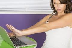 Ελκυστική συγκλονισμένη τρομαγμένη νέα γυναίκα που χρησιμοποιεί το φορητό προσωπικό υπολογιστή Στοκ Εικόνα
