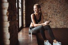Ελκυστική συνεδρίαση γυναικών ικανότητας στη μουσική ακούσματος γυμναστικής Στοκ Φωτογραφίες