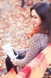 Ελκυστική συνεδρίαση γυναικών σε έναν πάγκο με μια ταμπλέτα Στοκ φωτογραφίες με δικαίωμα ελεύθερης χρήσης