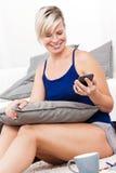 Ελκυστική συνεδρίαση γυναικών στο πάτωμα στο τηλέφωνο. Στοκ φωτογραφία με δικαίωμα ελεύθερης χρήσης