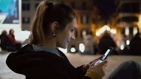Ελκυστική συνεδρίαση γυναικών brunette στο κέντρο της πόλης να εξισώσει και να φανεί φωτογραφία στο smartphone με την τεχνολογία  απόθεμα βίντεο