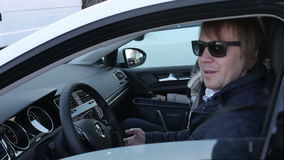 Ελκυστική συνεδρίαση νεαρών άνδρων πίσω από τη ρόδα ενός αυτοκινήτου και της ομιλίας στα μαύρα γυαλιά απόθεμα βίντεο