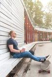 Ελκυστική συνεδρίαση νεαρών άνδρων στα ξύλινα βήματα σε έναν αστικό καφέ κατανάλωσης πάρκων πόλεων με τον κάνοντας πατινάζ πίνακά Στοκ Εικόνες