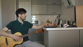 Ελκυστική συνεδρίαση νεαρών άνδρων στην κουζίνα που μαθαίνει να παίζει την κιθάρα που χρησιμοποιεί το φορητό προσωπικό υπολογιστή απόθεμα βίντεο