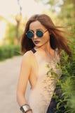 Ελκυστική σύγχρονη γυναίκα brunette με τα μπλε χείλια στα στρογγυλά γυαλιά ηλίου Στοκ Εικόνες