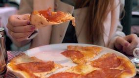 Ελκυστική φέτα εκμετάλλευσης γυναικών brunette της πίτσας και του δαγκώματος του Το πεινασμένο κορίτσι έχει ένα γεύμα στο εστιατό Στοκ Εικόνες