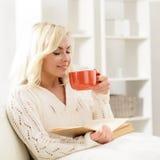 Ελκυστική χαμογελώντας ευτυχής γυναίκα που διαβάζει ένα βιβλίο Στοκ Εικόνα