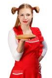 Ελκυστική χαμογελώντας νοικοκυρά στην κόκκινη ποδιά με τα αστεία ponytails α Στοκ Εικόνα
